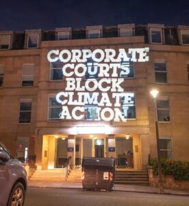 Projection of words 'corporate courts block climate action' on to the offices of law firm Clyde & Co in Edinburgh